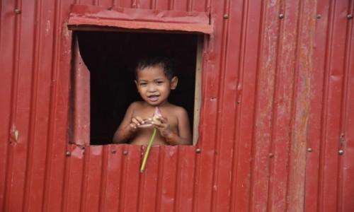 Zdjęcie KAMBODżA / - / wioska nad Tonle Sap / Chłopiec z kwiatem lotosu