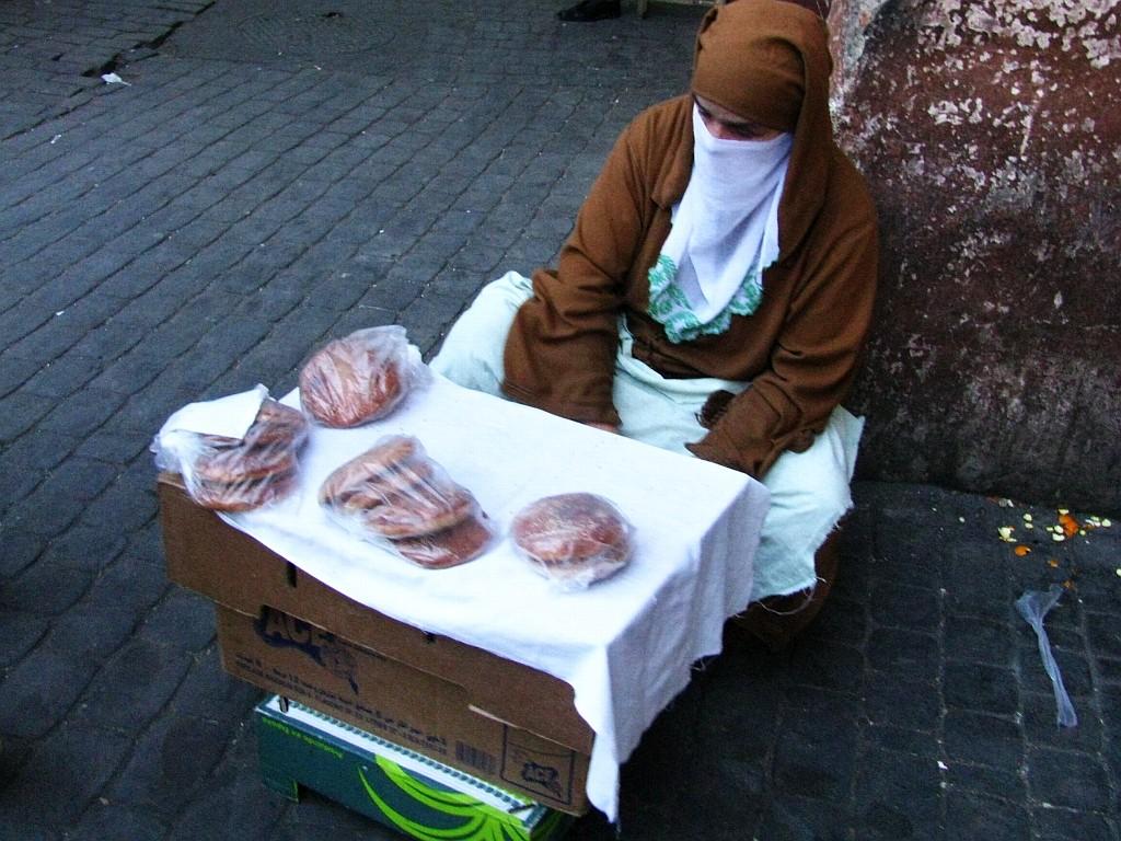 Zdjęcia: okolice Dżama el-Fna, Marrakesz, sprzedawczyni bułeczek, MAROKO