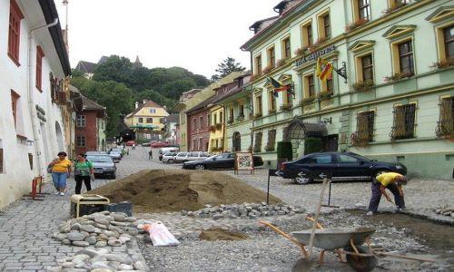Zdjecie RUMUNIA / Transylwania / Sighisoara /  naprawa, w tle  kościół na wzgórzu