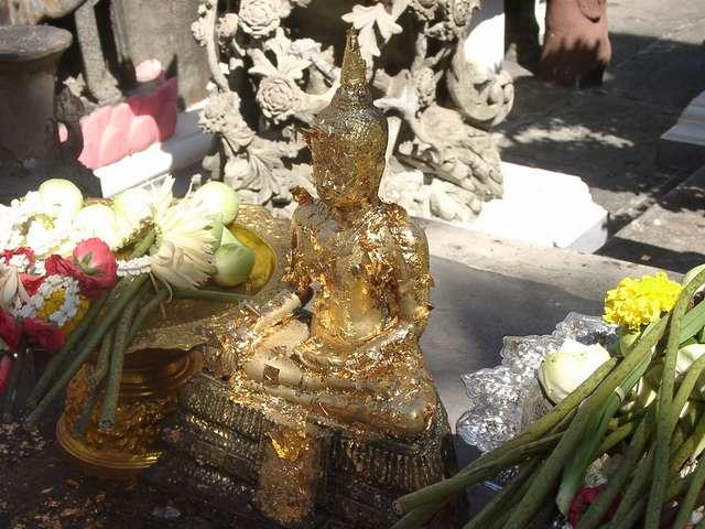 Zdj�cia: Bangkok, Modl�c si� o pieni�dze ludzie ofiarowuj� cienki pasek z�ota, kt�re przylepiaj� do pos��ka Buddy, TAJLANDIA